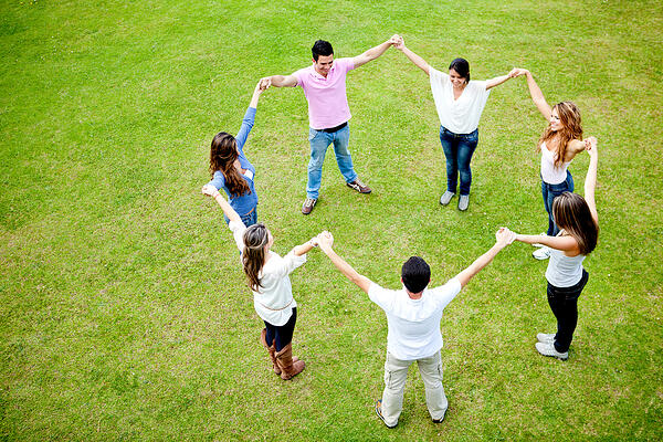 Group of people in a circle holding hands - outdoors